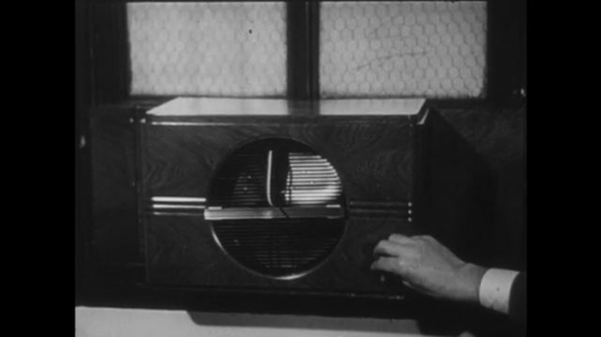 UNITED STATES 1940s: Hand turns on air conditioner / Sign outside business / Workers at desks in office.