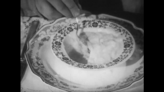 UNITED STATES 1950s: Close up of bowl of oatmeal, spoon scoops bite, hand pushes plate aways / Boy puts bacon on plate, eats.