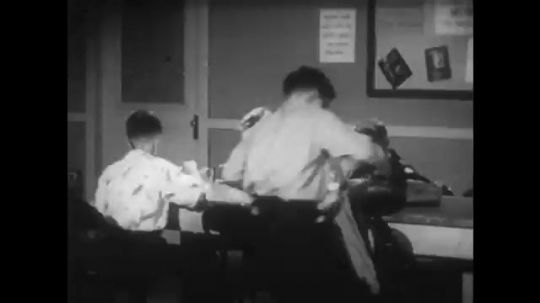 UNITED STATES 1950s: Kids eat at table, boy enters, digs in pocket, sits at table / Close up, boy eats sandwich.
