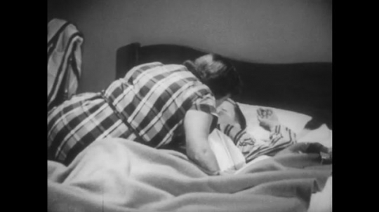 UNITED STATES 1950s: Woman kisses boy in bed, zoom out, woman turns out light / Boy tosses in bed, shots of food superimposed over image.