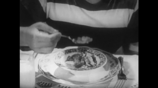 UNITED STATES 1950s: Close up, hands scoop from bowl of cereal / Plate of food, hands butter toast, zoom out, boy eats toast, smiles.
