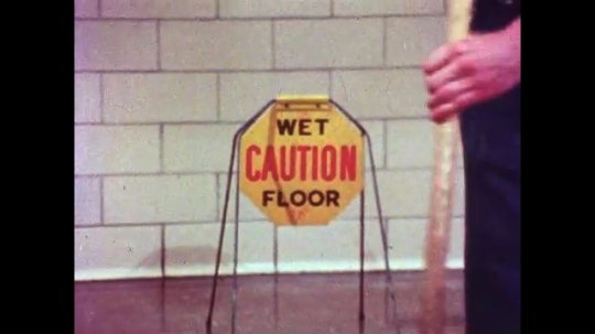 UNITED STATES, 1970s: 'Caution Wet Floor' sign. Man mopping hospital corridor floor. Sharps being placed in sharps bin.