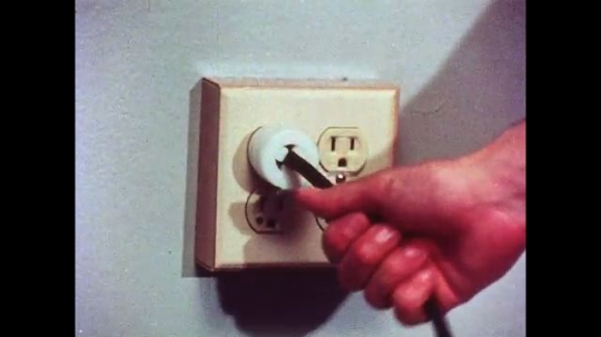 UNITED STATES, 1970s: Hand grabs wire on plug but stops. Hand moves from wire to plug before pulling it out of wall socket.
