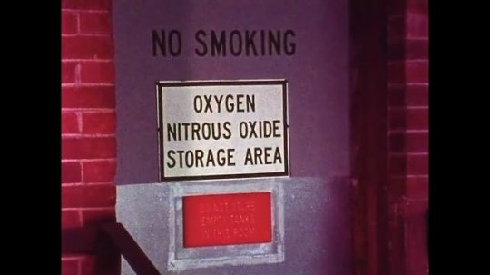 UNITED STATES, 1970s: No smoking sign next to oxygen, and nitrous oxide storage area. Man brings oxygen cylinder to oxygen storage area. Oxygen mask on pillow. Medic unscrews lid on oxygen cylinder.