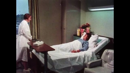 UNITED STATES, 1970s: Medic visits patient in bed, helps her up and prepares wheelchair for use. Lady transfers herself from the bed to the wheelchair in hospital room.
