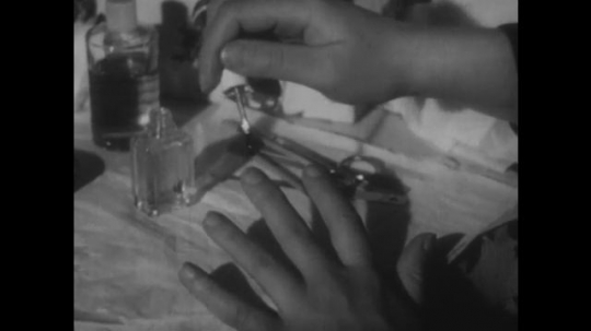 UNITED STATES 1940s: Close up of lady painting her nails. Lady blows on freshly painted nails. Lady screws cap on nail polish.
