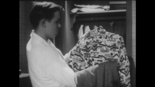 UNITED STATES 1940s: Young man looks at clothes in wardrobe and decides against shirt. Young man looks for shirt, tie, and trousers in cupboard.