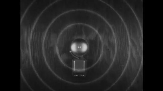 UNITED STATES, 1930s: Sound waves from a bell as hammer strikes it. Sound waves travelling through the air.