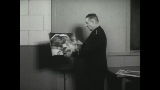 UNITED STATES, 1950s: Man in uniform puts photo on stand. Photo of car crash. Photo of car on ice. Photo of car in snow.
