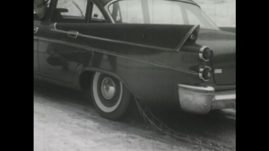 UNITED STATES, 1950s: Car drives forward as snow chains go around tyre. Man checks position of snow chain on car tyre. Car drives in snow with snow chains on tyres.