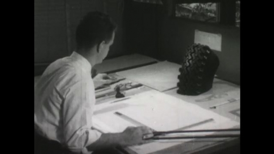 UNITED STATES, 1950s: Man at drawing board looks at model of tyre. Man points at treads on large trye and small cog. Car drives along snowy track