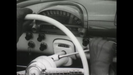 UNITED STATES, 1950s: Gloved hands operating steering wheel and car. Wheel stuck in snow. Car stuck in snow. Car moves out of snow and onto road.