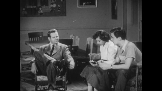 UNITED STATES: 1940s: Man looks on and listens as girl and boy talk and compare notes on sofa. Man sits in chair and thinks. Girl makes notes as boy talks.