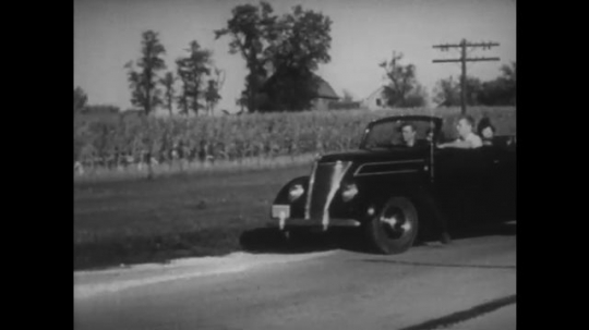 UNITED STATES: 1940s: Car pulls up on side of road. Boy looks at map and sees a house. Boy drives car.