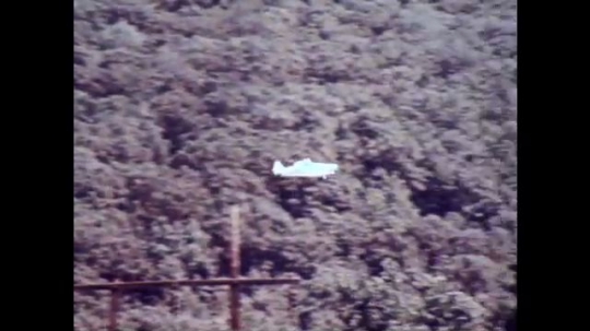 UNITED STATES, 1973: Airplane flies back and forth over treetops.