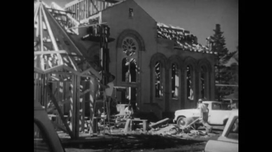 UNITED STATES, 1940s: Man pushing wheelbarrow on church building site. People at a building materials yard. Men arriving at a building.