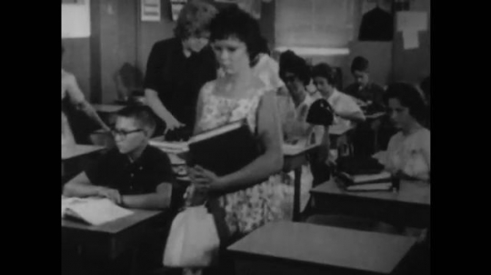 UNITED STATES, 1940s: People walking to seats in classroom. Man teaching class. Teenagers driving cars