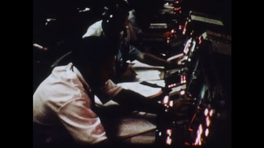UNITED STATES 1970s: Men in control room / Close up, hands press buttons / Man looks in book, picks up phone.