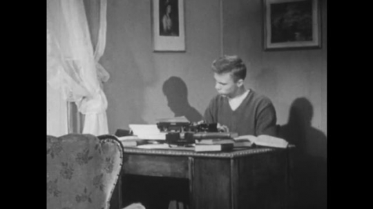 UNITED STATES, 1951: Boy sits at desk and uses a typewriter.