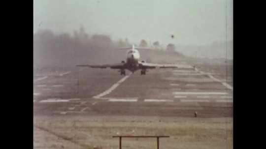 UNITED STATES 1970s: Plane takes off, zoom out, plane flies overhead / Flight control tower / Men inside flight tower.