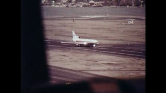 UNITED STATES 1970s: Panning shot from control tower, plane takes off from runway.