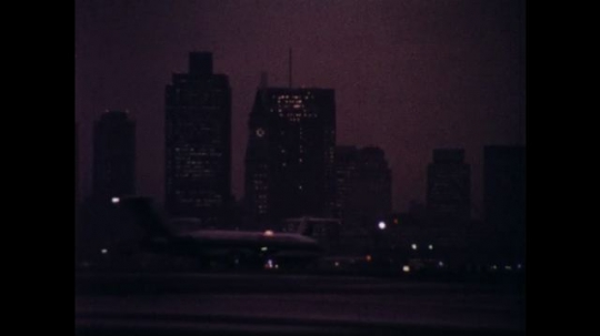UNITED STATES 1970s: City skyline, planes on runway / Reporters in room, zoom out to meeting / Close up of man talking.
