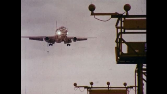 UNITED STATES 1970s: Plane flies over metal fence / Plane flies over neighborhood, pan to street / Plane flies over house.