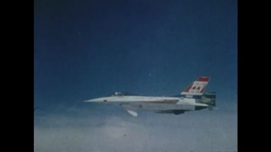UNITED STATES: 1980s: Two jet planes fly parallel in sky. Jet plane flies above ground. Jet plane with moon behind. Jet plane in desert with mountains behind.