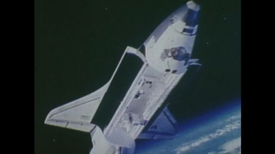 UNITED STATES: 1980s: Space shuttle floats in space. Animation of satellite in space. Images of satellite flying in space over Earth.