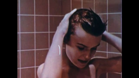 UNITED STATES: 1950s: Boy in shower runs fingers through his hair. Boy puts shampoo in his hair as he takes a shower. Close up of boy