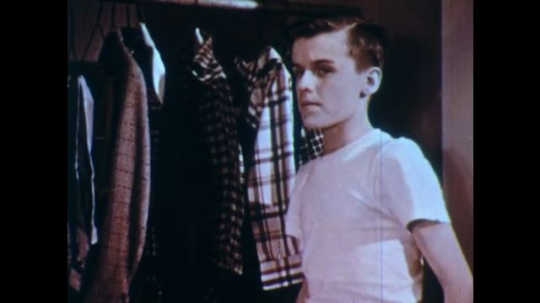 UNITED STATES: 1950s: Boy chooses which shirt to wear. Boy puts shirt on. Boy smiles at camera and combs hair. Boy admires self in mirror.