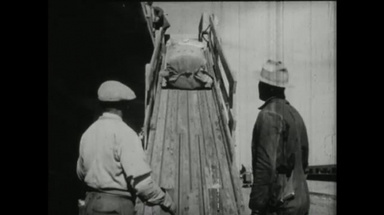 UNITED STATES, 1940s: sacks of cotton dropped down shoot to men below. Cotton on industrial spinning loom.