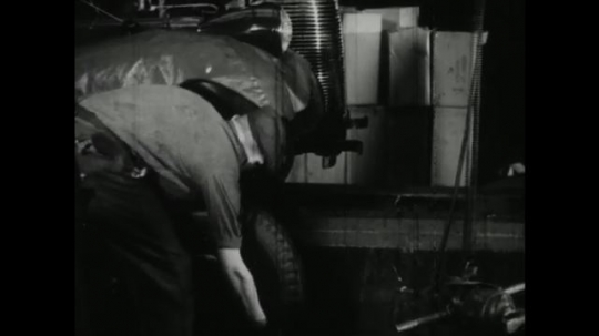 UNITED STATES, 1940s: factory worker picks up tyre and puts on machine. Man lays out raw textiles