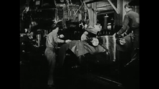 UNITED STATES, 1940s: car loaded onto conveyor belt in factory