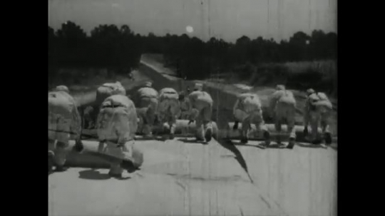 UNITED STATES, 1940s: men push rolls of textile along road surface