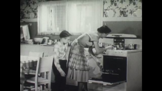 UNITED STATES: Mother glazes food in the oven as boy licks his lips.