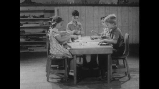 UNITED STATES 1940s: Kids playing at table / Kids at tables in classroom, boy stands.