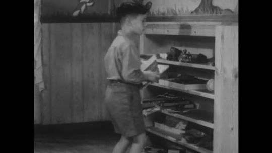 UNITED STATES 1940s: Boy puts toys on shelf / View of shelves.