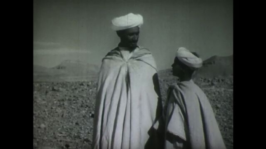 MIDDLE EAST: 1940s: Man and boy talk as they watch sheep in desert. Man flicks material over shoulder. Man and boy watch flock. Family set up camp in desert.