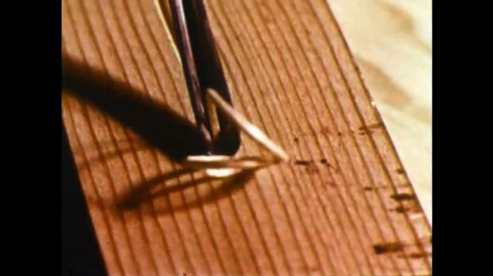 UNITED STATES 1960s: Close up, hand scratches into wood / Hands roll out clay / Clay shaped into a coil.
