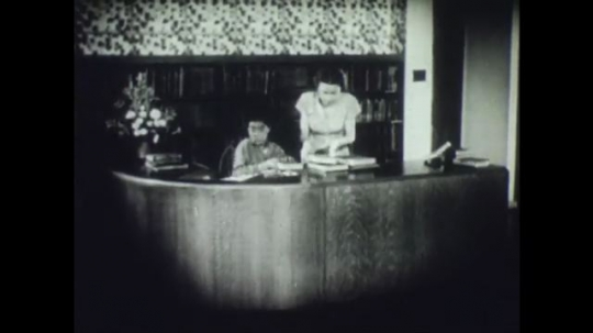 United States, 1940s: Boy helps librarian and customers with books in library. Boy signs out library book for customer. Lady sorts through library cards.