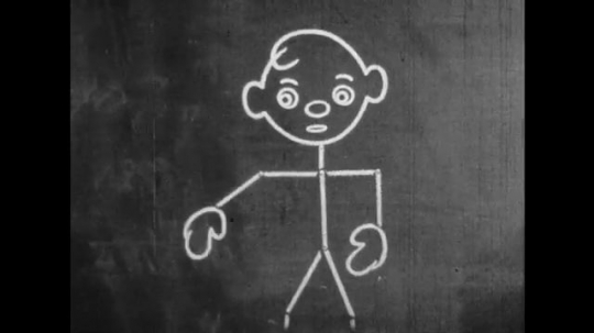 UNITED STATES: 1950s: Chalk drawing of man moves arms. Boy picks up chalkboard brush. Boy chases cartoon man around blackboard.