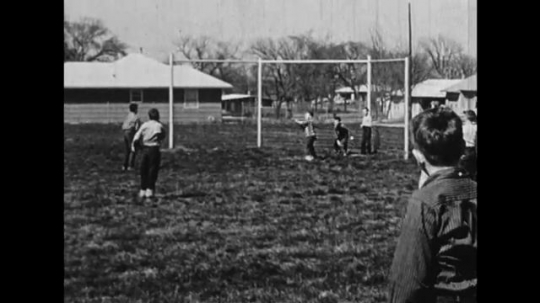 UNITED STATES: 1950s: Children play ball games in playground. Boys argue over baseball bat.  Boy hits ball with baseball bat.