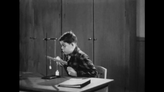 UNITED STATES: 1950s: Boy tidies away science apparatus. Boy opens cupboard.