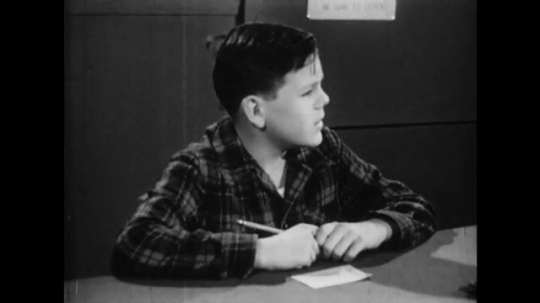 UNITED STATES: 1950s: Boy looks around room and thinks. Poster advertises radio forum. Students meet in groups. Students play sports