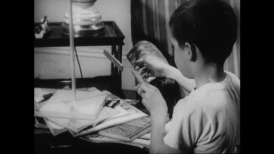 UNITED STATES 1950s: Boy plays with magnet on string / Dissolve, sign for magic show, tilt up to boy performing for kids / Close up, hand moves toy boat with magnet.