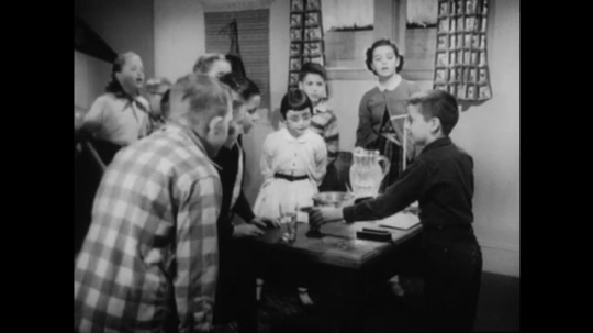UNITED STATES 1950s: Boy at table with kids, kids raise hands, sit down / Boy hangs magnet on string / Close up, hands hold magnets together.