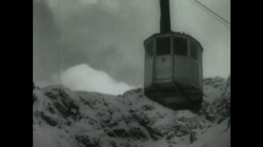 POLAND, 1950s: Cable car moving above fields and woods covered in snow. Shadow of cable car on trees below.