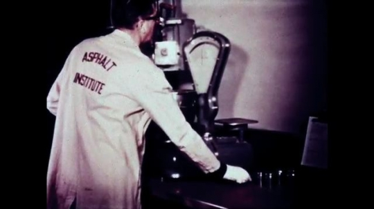UNITED STATES: 1940s: Man in lab coat puts substance in pot and on oven to heat up.