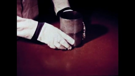UNITED STATES: 1940s: Man splits two cans and their ingredients apart.